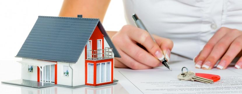 Eine Frau unterschreibt einen Kaufvertrag für ein Haus bei einem Immobilienmakler.
